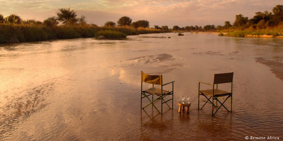 Two camp chairs and wine glasses laid out in the Luangwa River for sundowners at sunset on safari in the Luangwa Valley