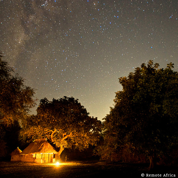 Thatched hut in orange light surrounded by trees and a dark sky of stars on safari with Remote Africa in Luangwa Valley