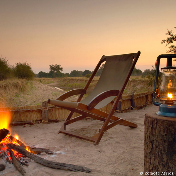 Deck chair and hurricane lamp in the sand next to a campfire overlooking the riverbed at sunset on safari in Luangwa Valley