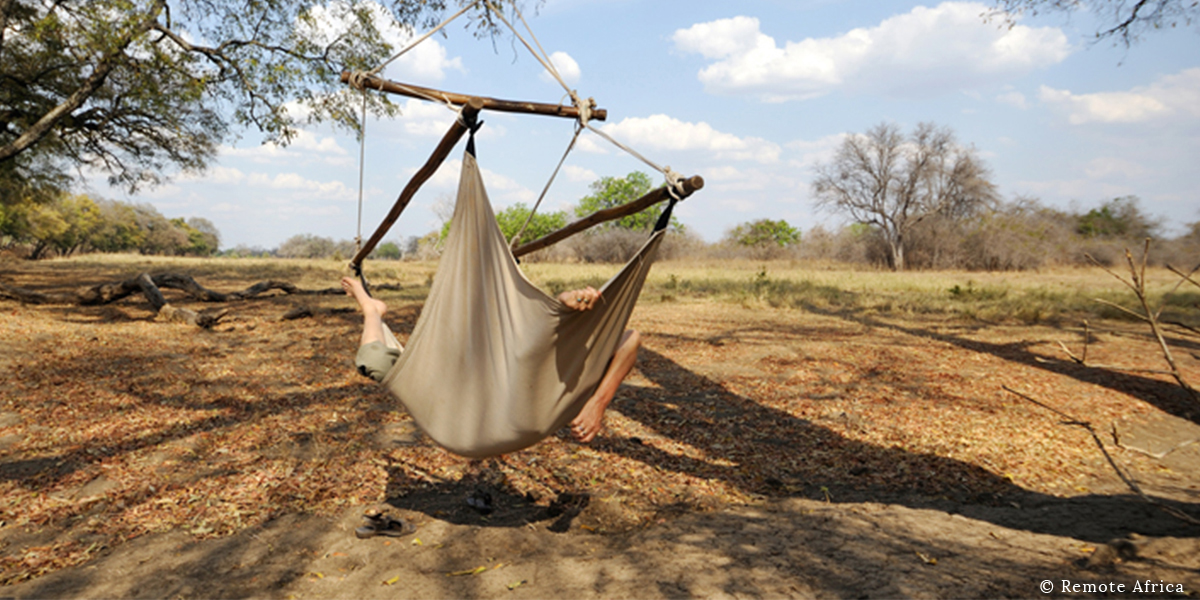 Person relaxing in a hammock in the dappled shade, looking out over the bush on safari with Remote Africa in Luangwa Valley