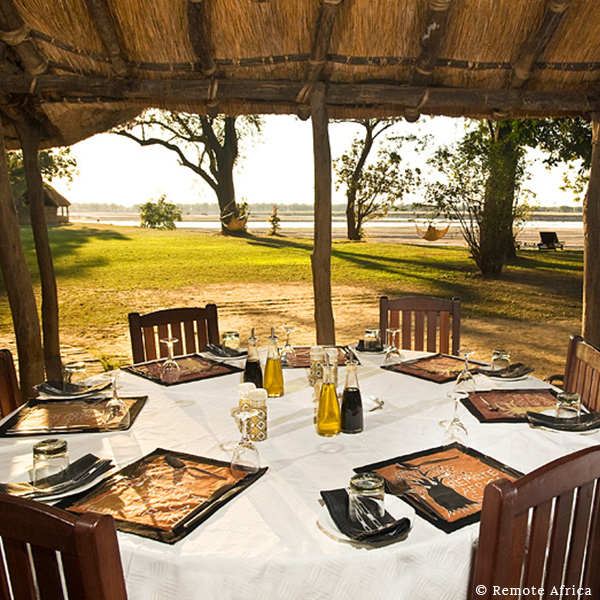 Table laid with ethnic painted placemats under a thatched roof on safari with hammocks and the Luangwa River in the distance