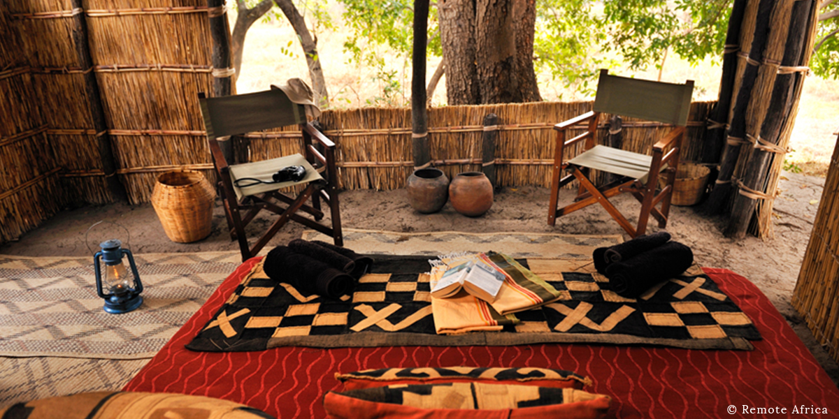 Interior of rustic hut at the lodge, Remote Africa, with two campaign chairs, safari gear, and a bed with an ethnic quilt