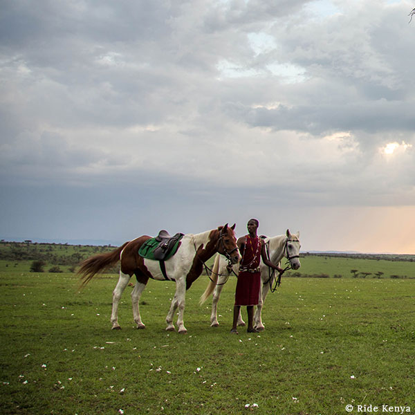 Maasai man in a red shuka standing with two horses in a plain under a moody, cloudy sky on a horse safari with Ride Kenya