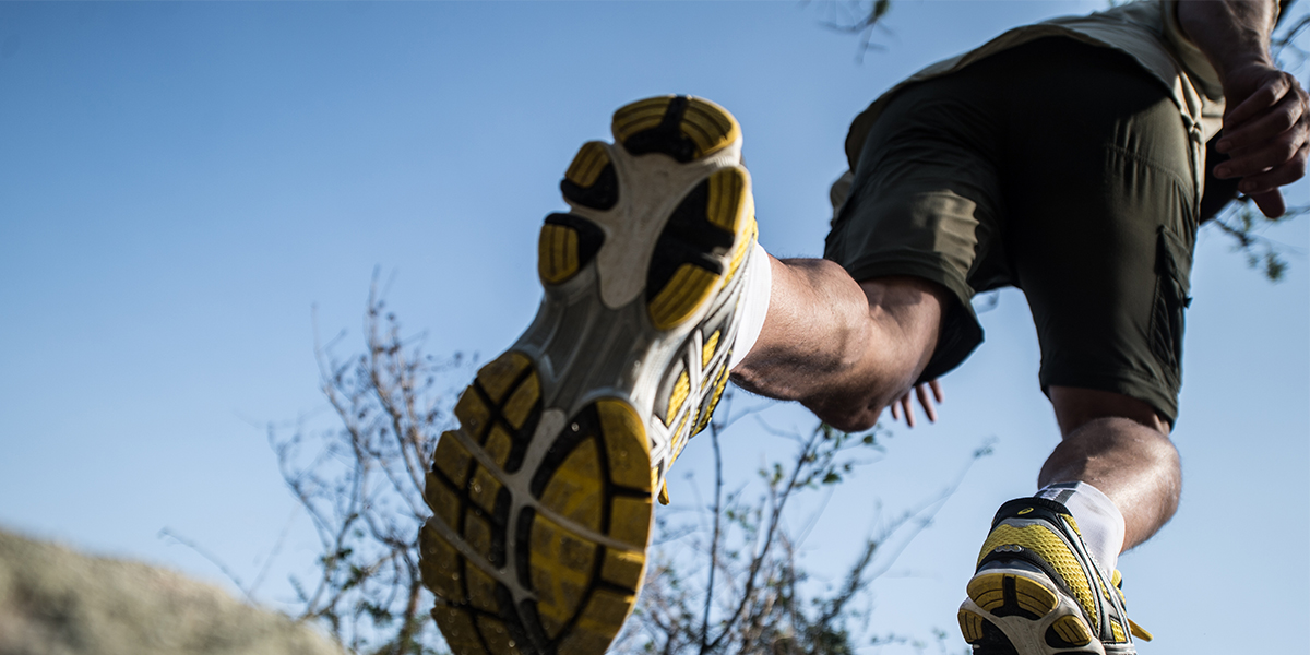 The legs of a man in running shoes and running clothes trail running through the bush on an active safari in Africa
