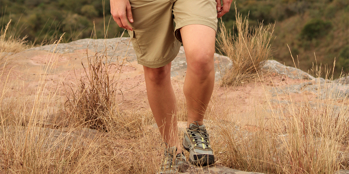 A woman wearing safari shorts and Merrell Safari Walking Shoes on a rocky, grassy trail when running on safari in Africa