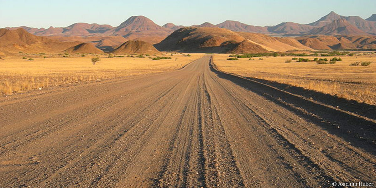 A long dirt road in the Namib desert in Africa