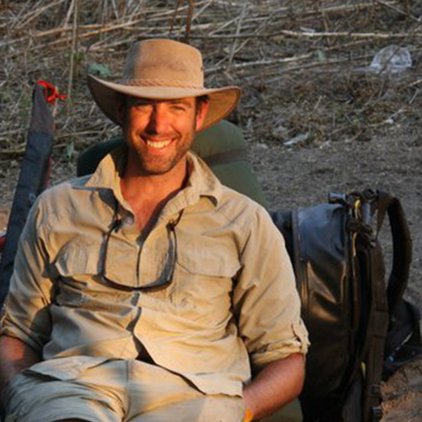 A smiling man wearing a hat and safari clothing