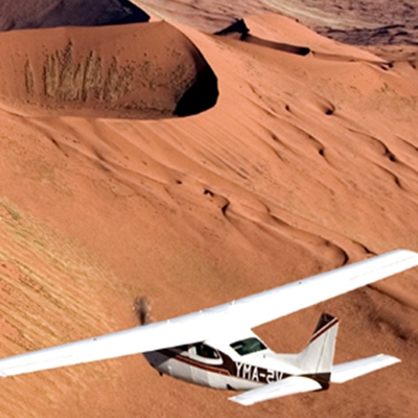 A small white airplane flying over the Namib desert