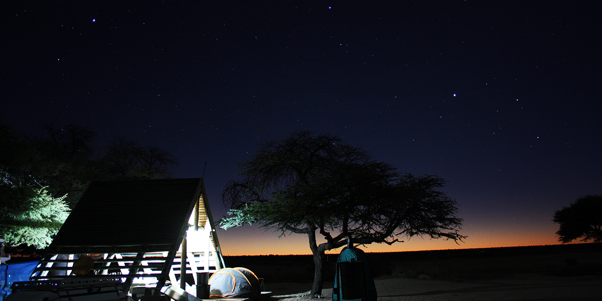A lit up campsite in the Kgalagadi Transfrontier Park at sunset with a wooden structure, tent and camp shower under a tree