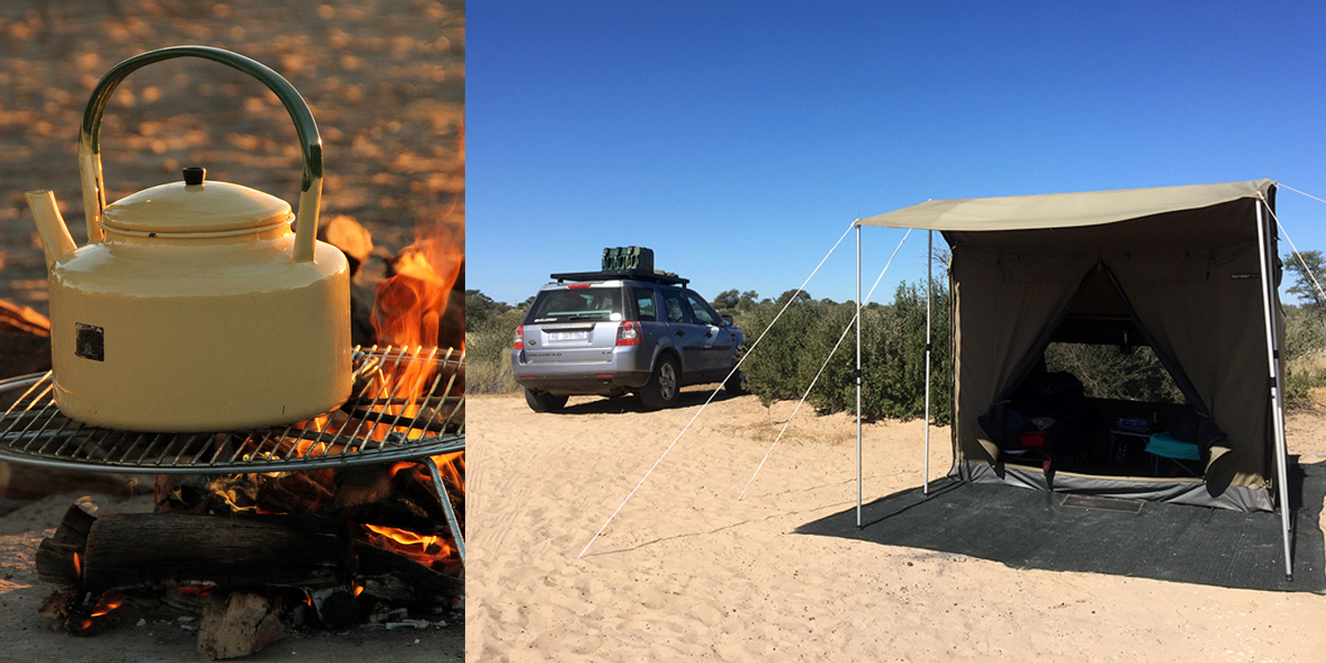 An enamel kettle on a grid over a campfire and a blue Landrover parked next to a canvas tent in Kgalagadi, Botswana