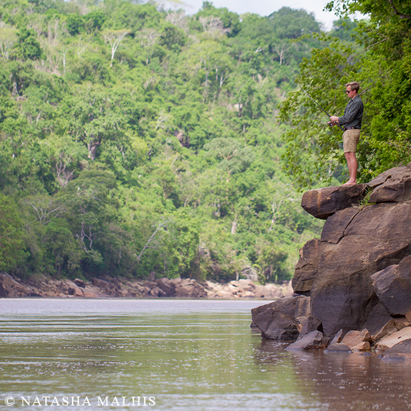 A man, Eric Jones, fishing from the top of a big rock