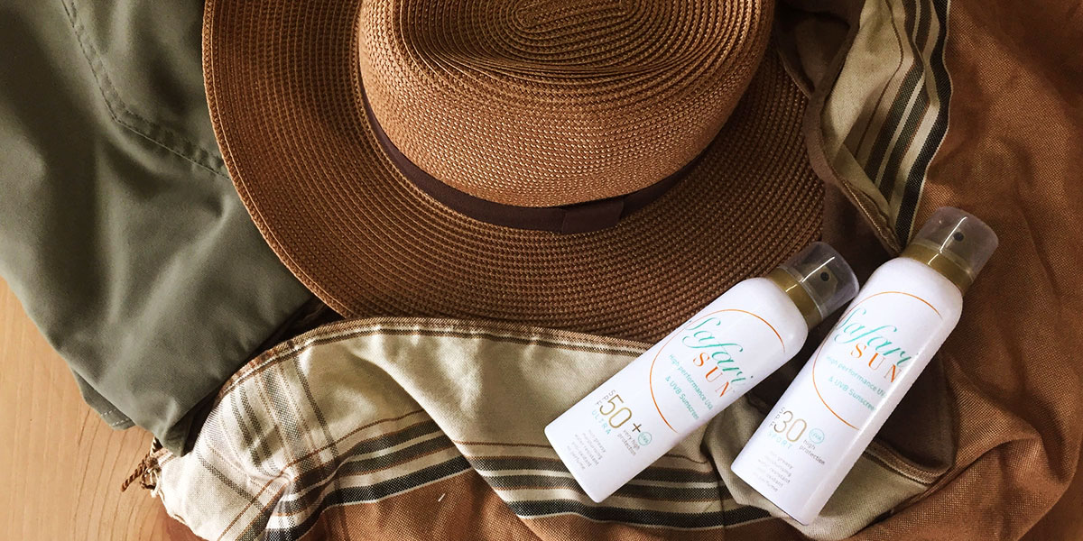 Two bottles of sunscreen, an SPF50 and SPF30, next to a brown scarf and safari hat.