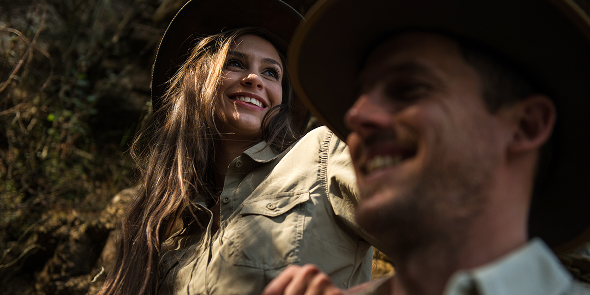 A smiling woman and man wearing wide-brimmed hats and safari clothing