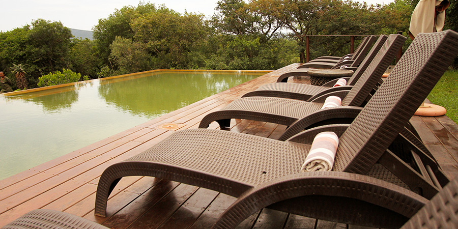 An infinity pool with loungers and guest towels at a lodge in Africa