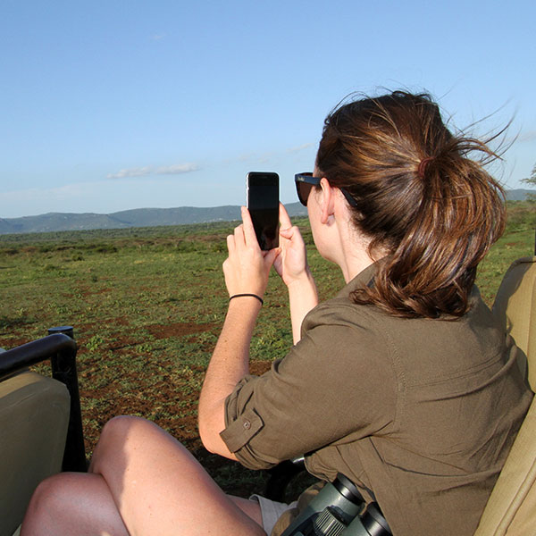 A woman on safari in Thanda Game Reserve taking pictures with her iPhone. A pair of Swarovski binoculars are on her lap.