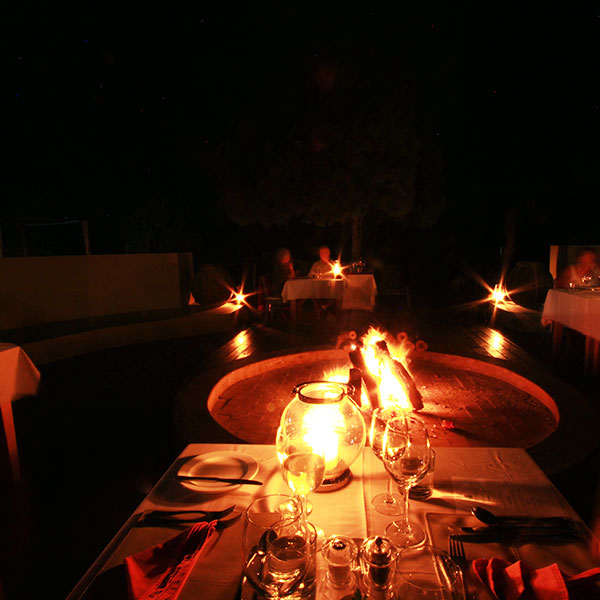 An luxury ambient safari dinner with lanterns and a warm fire.