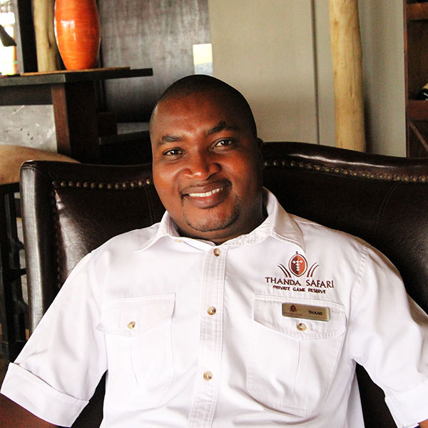 The manager of Thanda Bush Camp in a branded white shirt and name tag smiles for the camera.