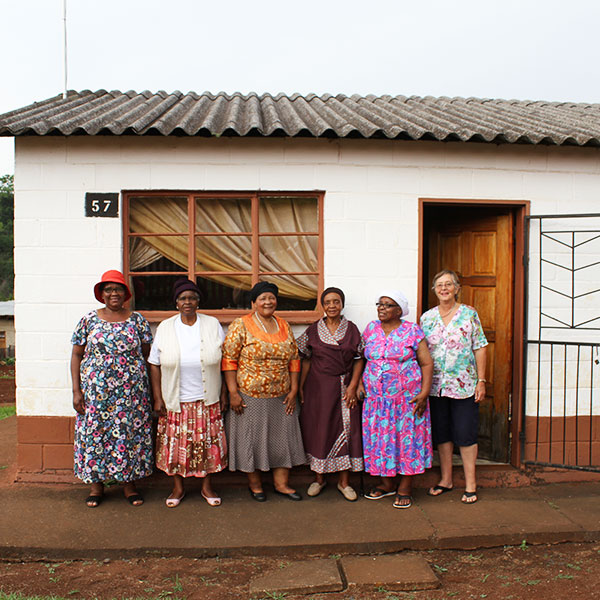 Six women wearing floral dresses stand in front of a small house with the number 57 next to the window.