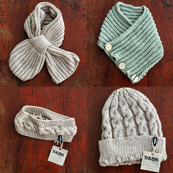 A variety of knitwear in soft browns and greens: a bow scarf, a button scarf, a headband and a beanie.