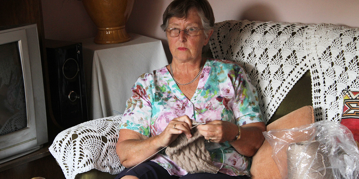 A woman wearing a floral shirt sits on a sofa and knits a beanie.
