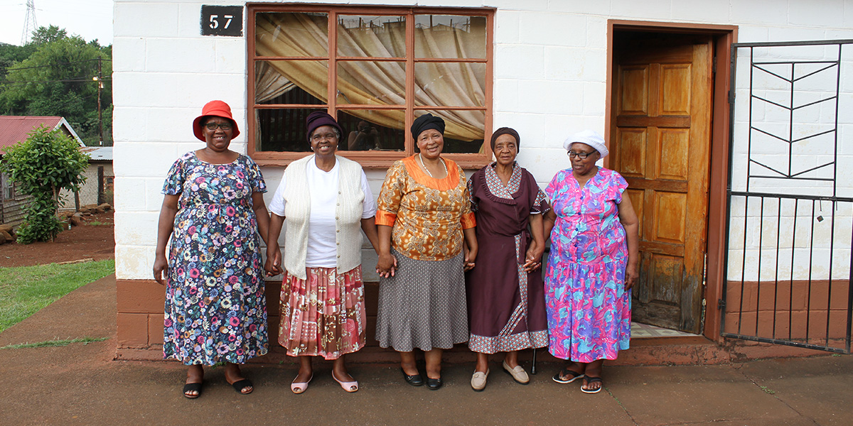 A group of women standing in front of a small house holding hands.