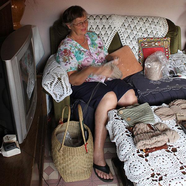 A woman sitting on a sofa knitting a beanie.