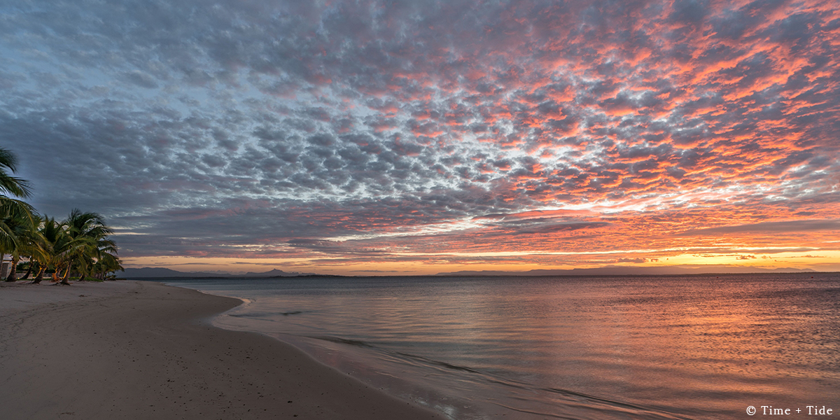A beach with palms and the sea and clouds lit with colour at sunset at Time + Tide Miavana, Nosy Ankao, Madagascar