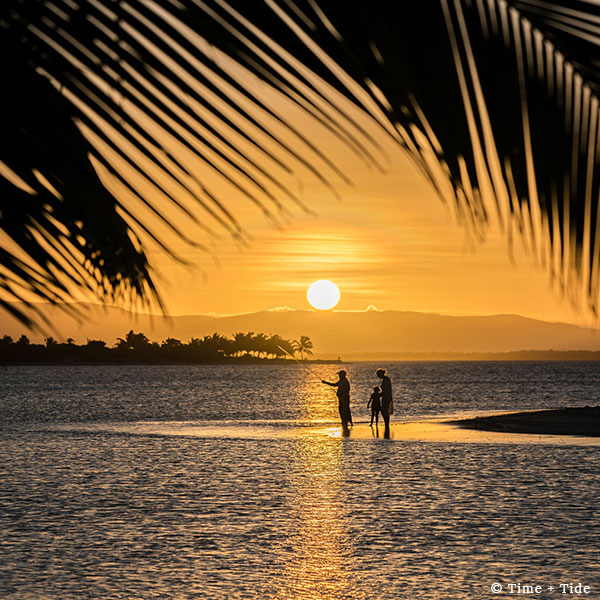 Sunset view through silhouetted palm leaves overlooking a family standing and fishing off a sandbank with palms behind them