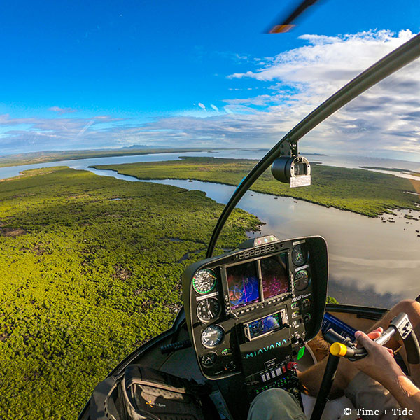 Helicopter cockpit in the air overlooking river channels and coastal bush with Time + Tide Miavana, Nosy Ankao, Madagascar