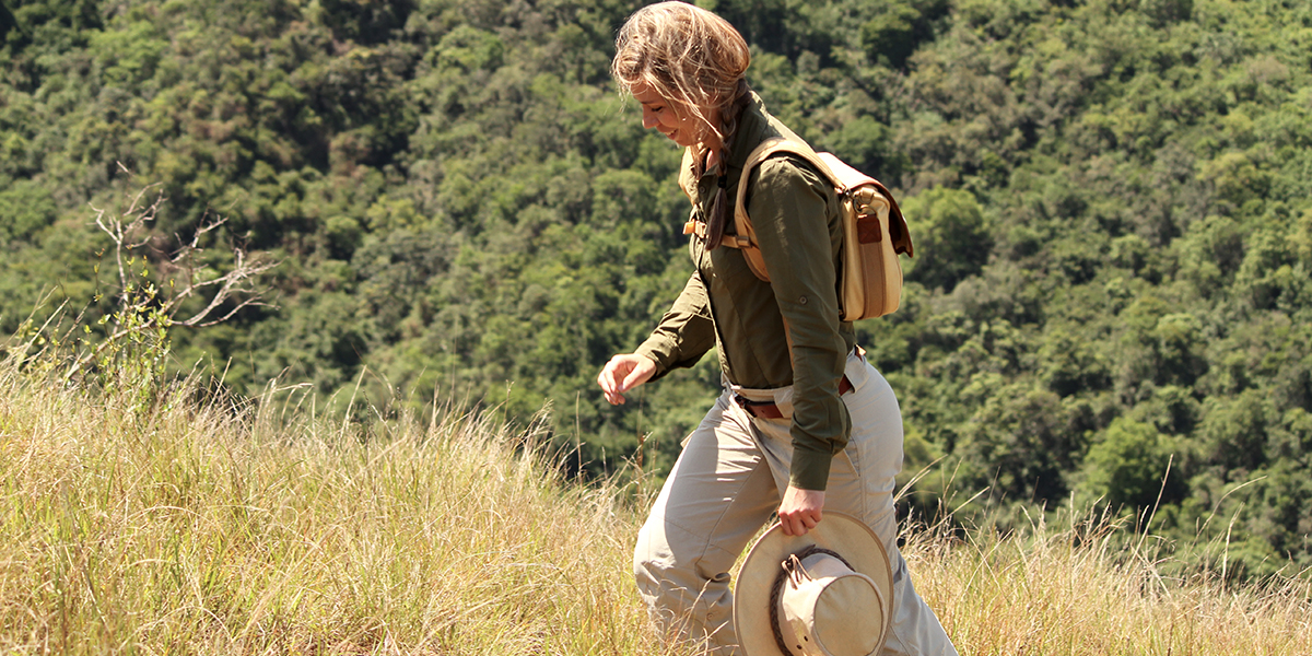 A woman climbing a hill wearing safari clothing and carrying a hat and a canvas and leather backpack on a walking safari