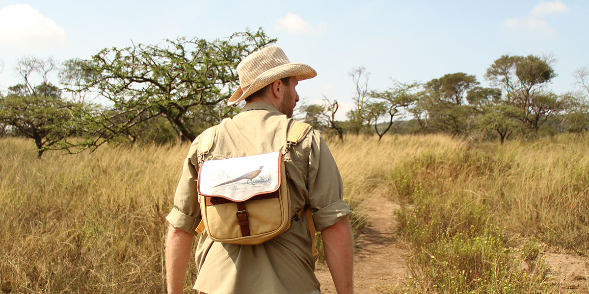 A man in a safari shirt and safari hat wearing a canvas and leather backpack with a pheasant flap on a walking safari