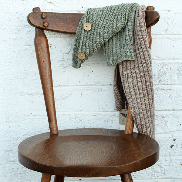 A pale green scarf with wooden buttons and a light brown scarf draped over a rustic wooden chair
