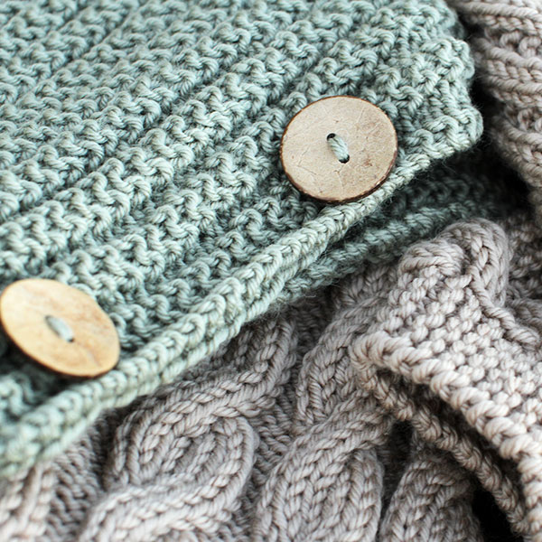 Close-up of a pale green knitted scarf with wooden buttons
