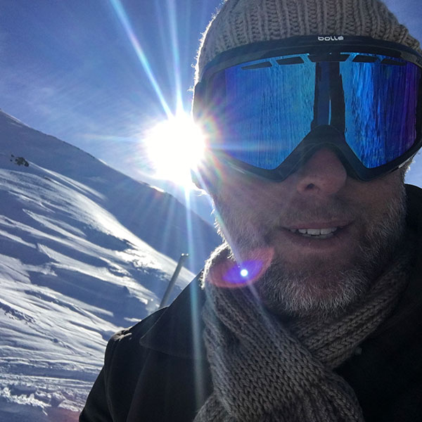 A selfie of a man in a ski mask wearing a knitted beanie and scarf while on a skiing holiday in snowy mountains