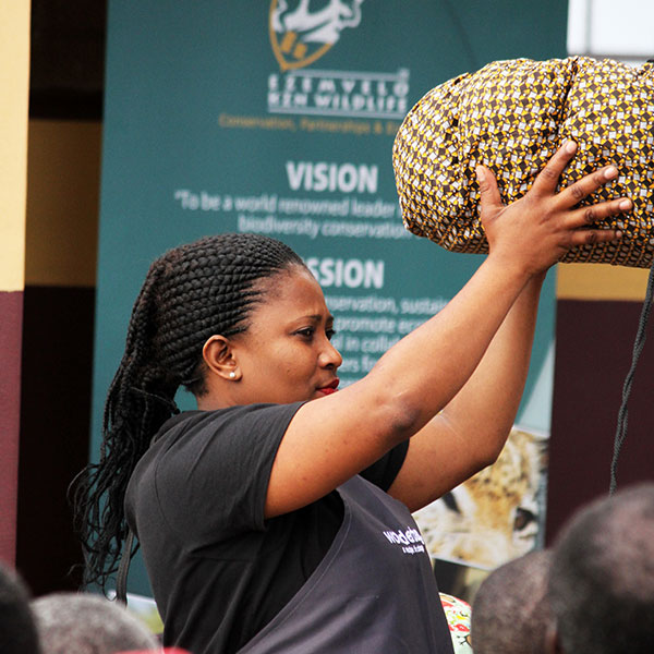 A lady from the Wonderbag team holding up a bag to demonstrate how it works.