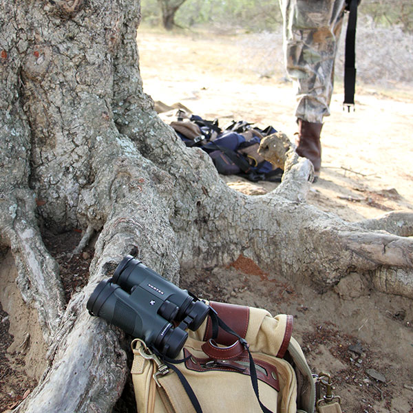 A pair of Vortex binoculars resting on a canvas satchel bag against a tree.