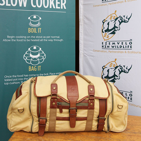 A safari and travel canvas and leather holdall in front of Ezemvelo KZN Wildlife and Wonderbag promotional banners.
