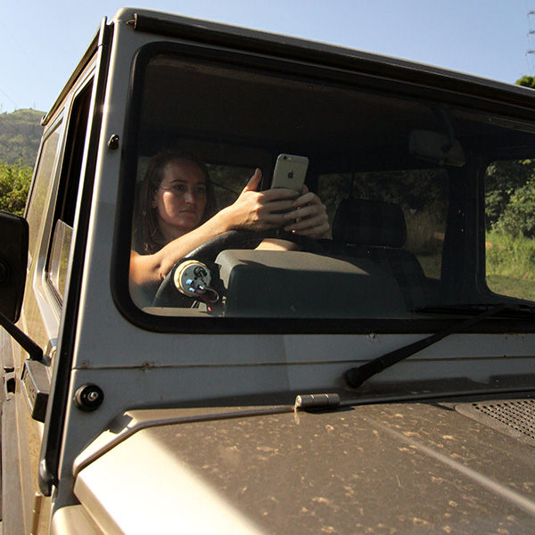 A woman in a Mercedes G-wagen 4x4 using her iPhone GPS to navigate while on safari.