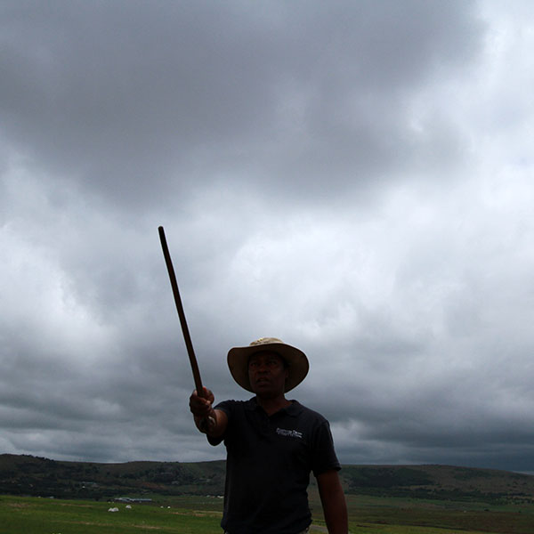 Our guide to Isandlwana, Mphiwa, framed by dark clouds looming above the mountains.