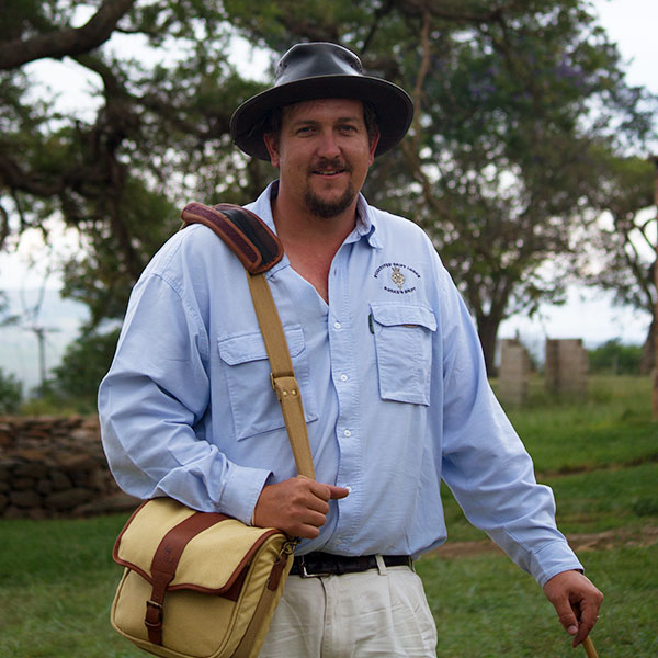 Andrew Rattray wearing a wide-brimmed hat and canvas satchel posing with his tour guiding stick