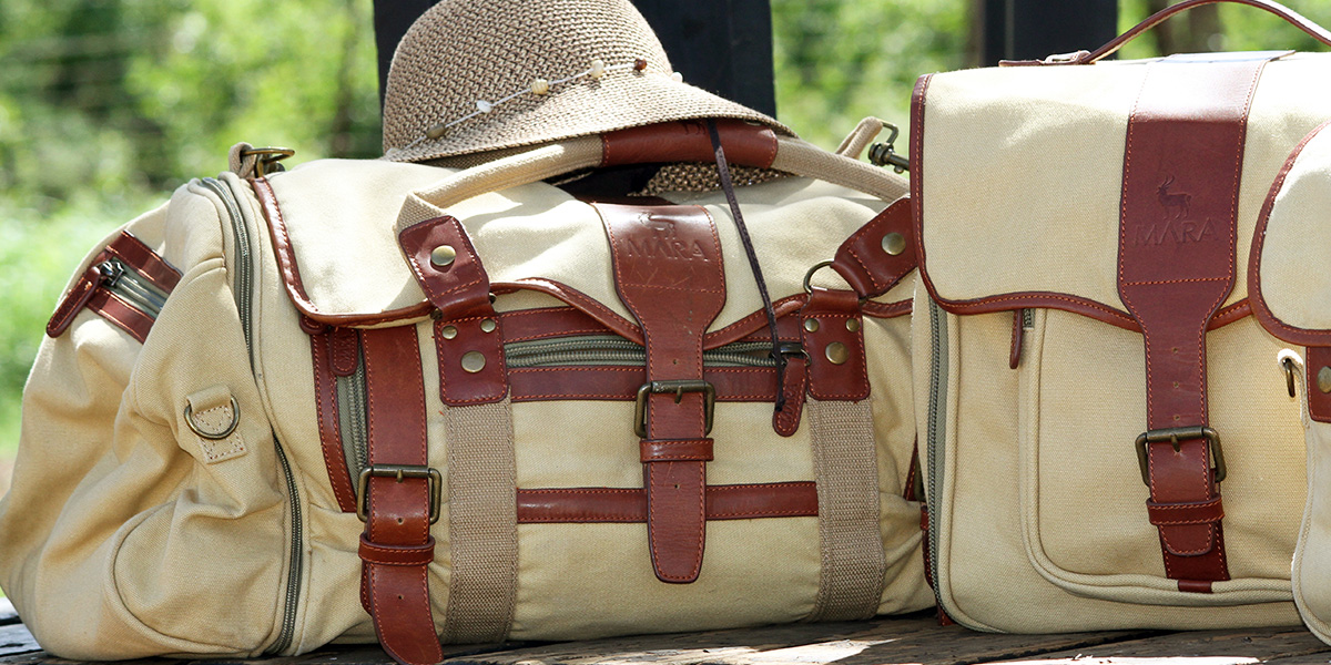 Close-up of canvas and leather safari luggage with a woman's hat on the duffel bag