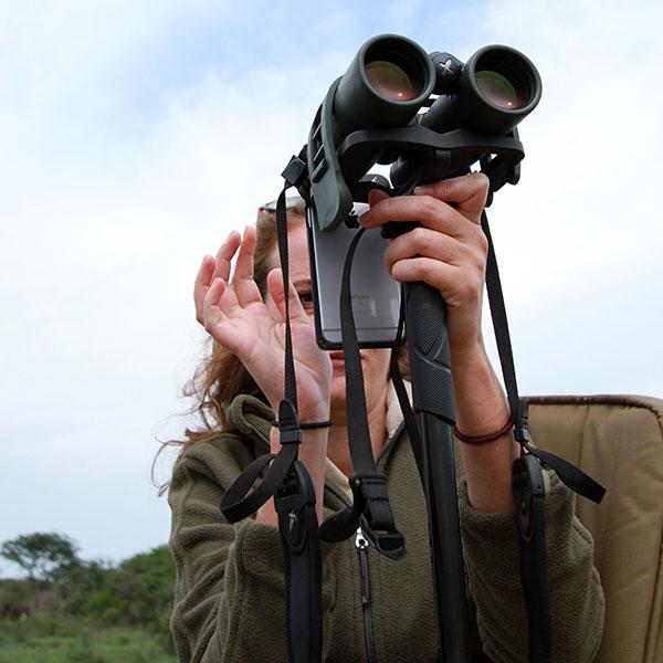 A woman on a safari vehicle using her iPhone to take photos through a pair of Swarovski binoculars