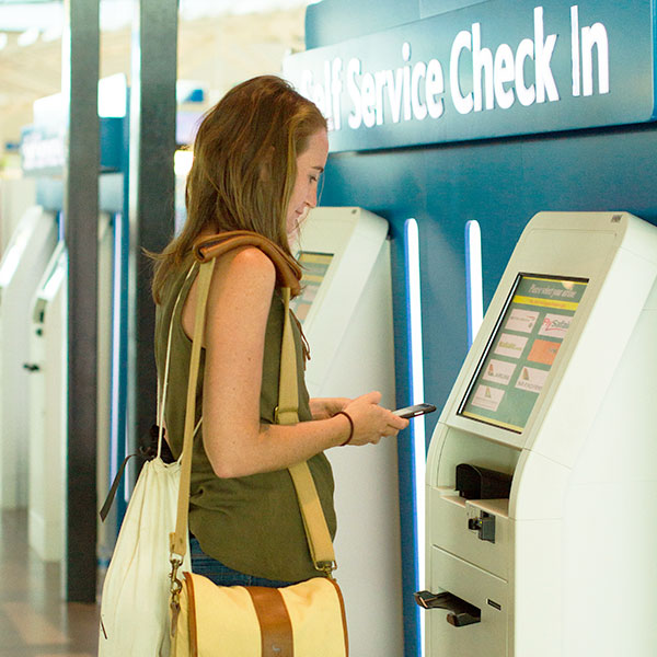 A woman carrying bags using her iPhone 6 smartphone and the self service console to check in at an airport.