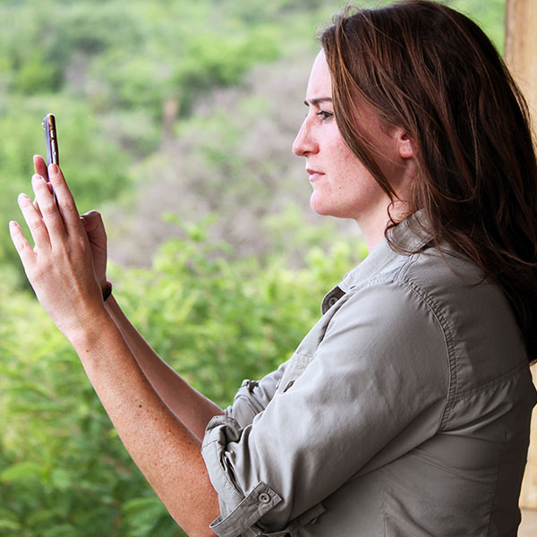 A woman wearing a safari shirt holds up an iPhone smartphone to take a photo.