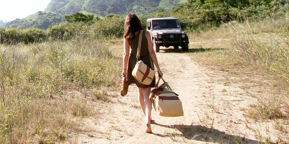 A woman walks towards a Mercedes G Wagon carrying a tan canvas satchel and safari duffel bag.