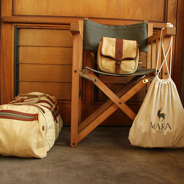 A khaki director's chair surrounded by safari canvas luggage including a duffel, drawstring bag and satchel.