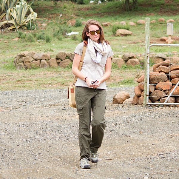 A woman wearing cargo trousers, a gilet fleece and snood carrying a canvas satchel and a smartphone walks on a dirtroad.
