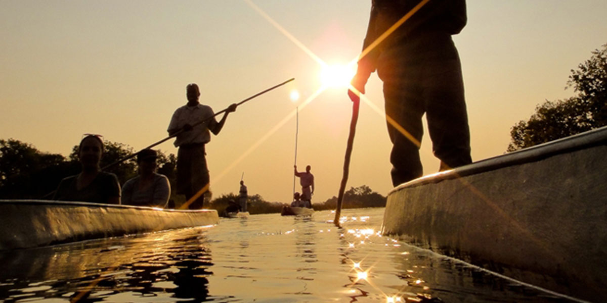 People rowing canoes at sunset on the golden waters of the Okavango Delta in Botswana