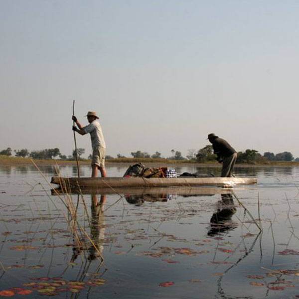 Two men poling a mokoro on the clear waters of the Okavango Delta in Botswana
