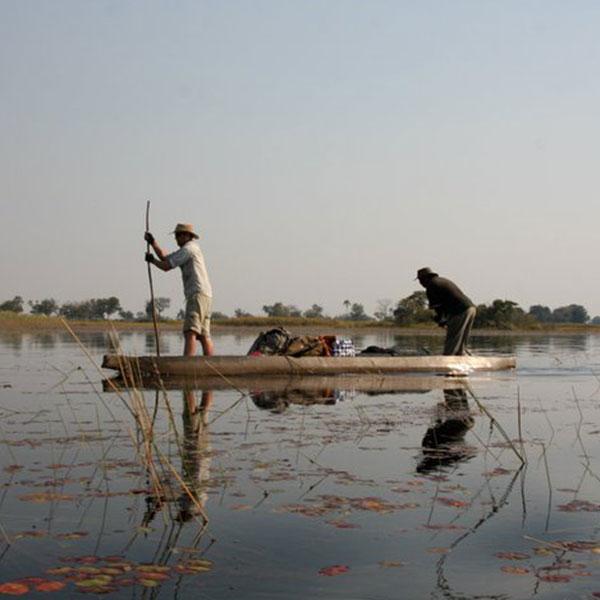 Two men poling a mokoro on the clear waters of the Okavango Delta in Botswana